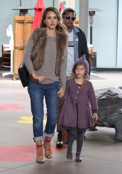 Jessica Alba is comfy for day in a furry vest layered overtop a sweater and slouchy jeans, with high heeled booties.