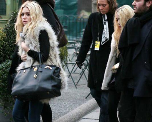 Ashley Olsen and Mary Kate Olsen wearing fur vests.