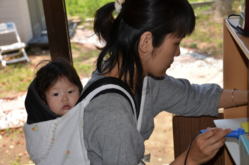 nozomi project woman with child making jewelry