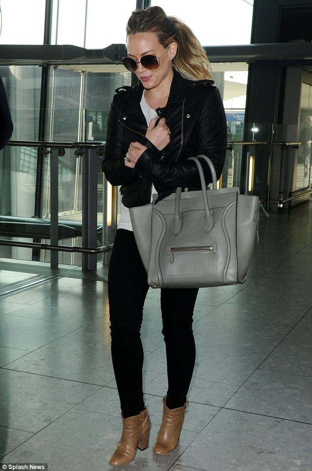 Hilary Duff carries a pastel gray, oversized Celine mini luggage.