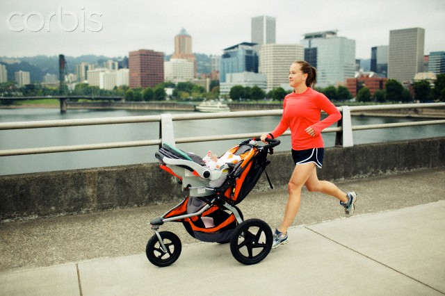 New Mom Workout - Mother running with baby in stroller on city bridge