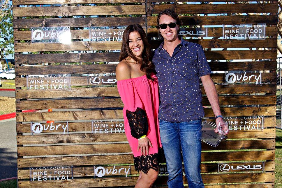 couple poses on step and repeat at wine festival